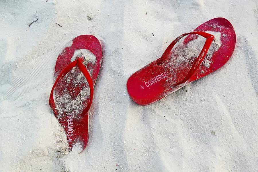 par de chinelos vermelho visto de cima com areia