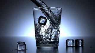 um refrestante copo com água e gelo
