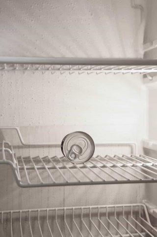 Geladeira com nada dentro a não ser com uma lata de refrigerante dentro