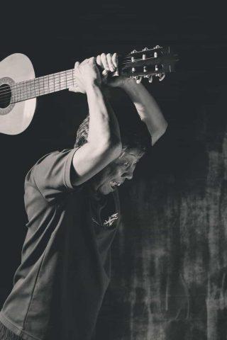 Homem irritado com guitarra na mão