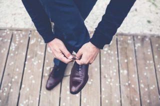 Um rapaz magro amarrando os sapatos muito bem limpo e polidos