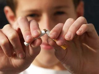 menino quebrando cigarro no meio