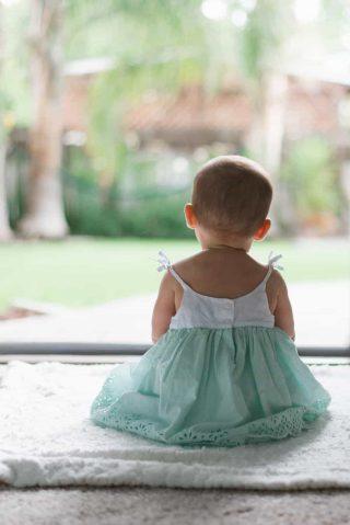Criança peuena sentada vendo paisagem com vestido branco e verde